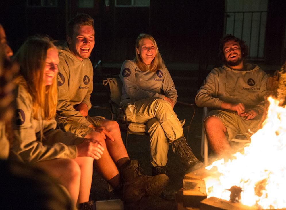 Group of people sitting around a fire