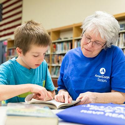 Lady wearing an AmeriCorps Seniors T-shirt reading with a small boy