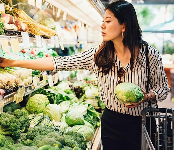 Woman in a grocery store looking at vegetables