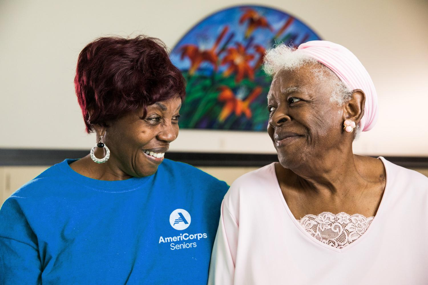 AmeriCorps Seniors volunteer with fellow senior, laughing at senior's house