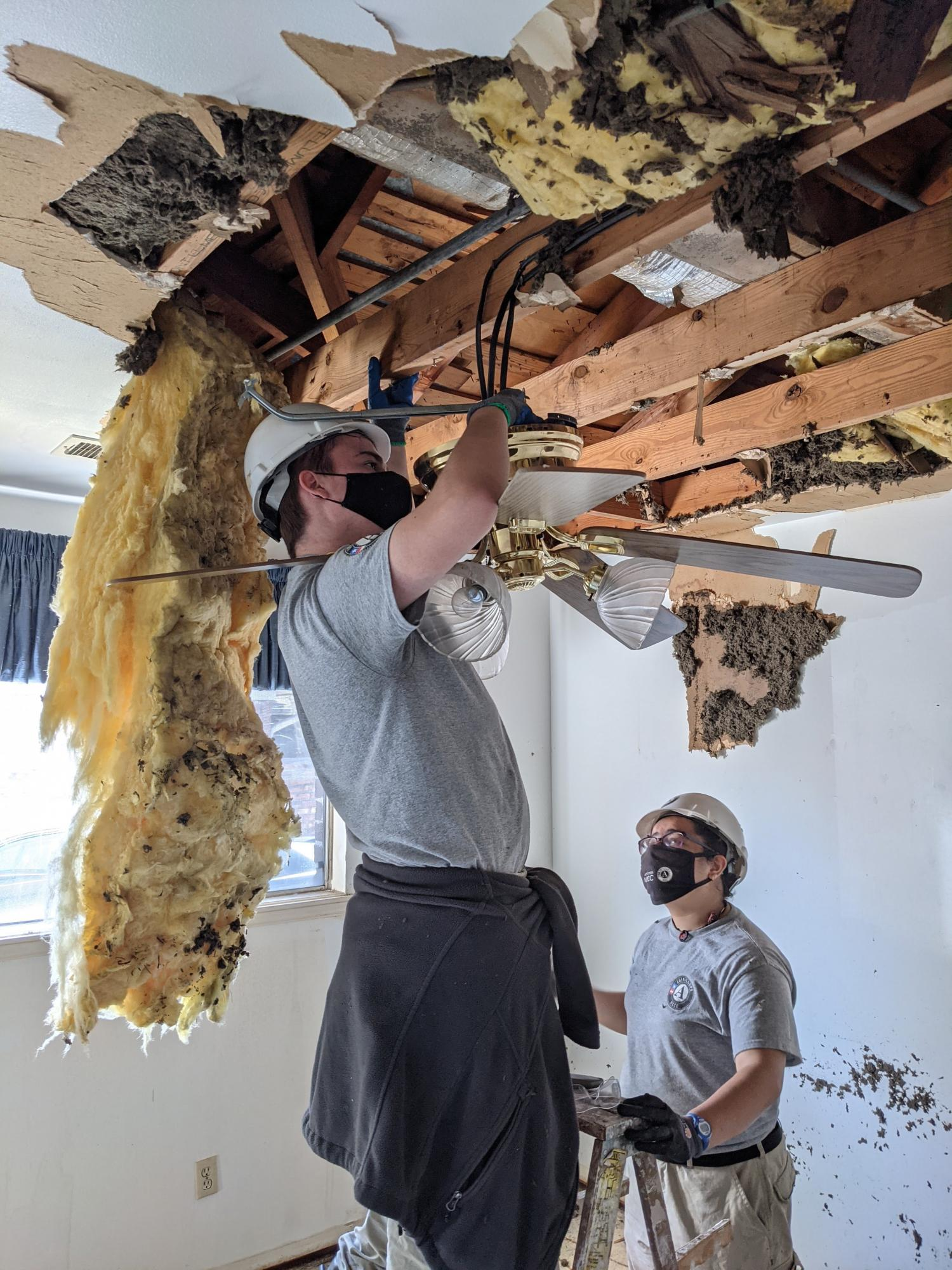 NCCC members remove waterlogged insulation from Houston home.