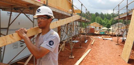 Man wearing an AmeriCorps T-shirt carrying a plank of wood on a building site