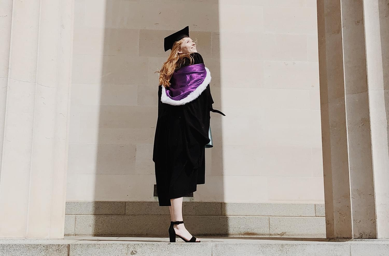Woman wearing a mortar board hat and gown standing in front of a building