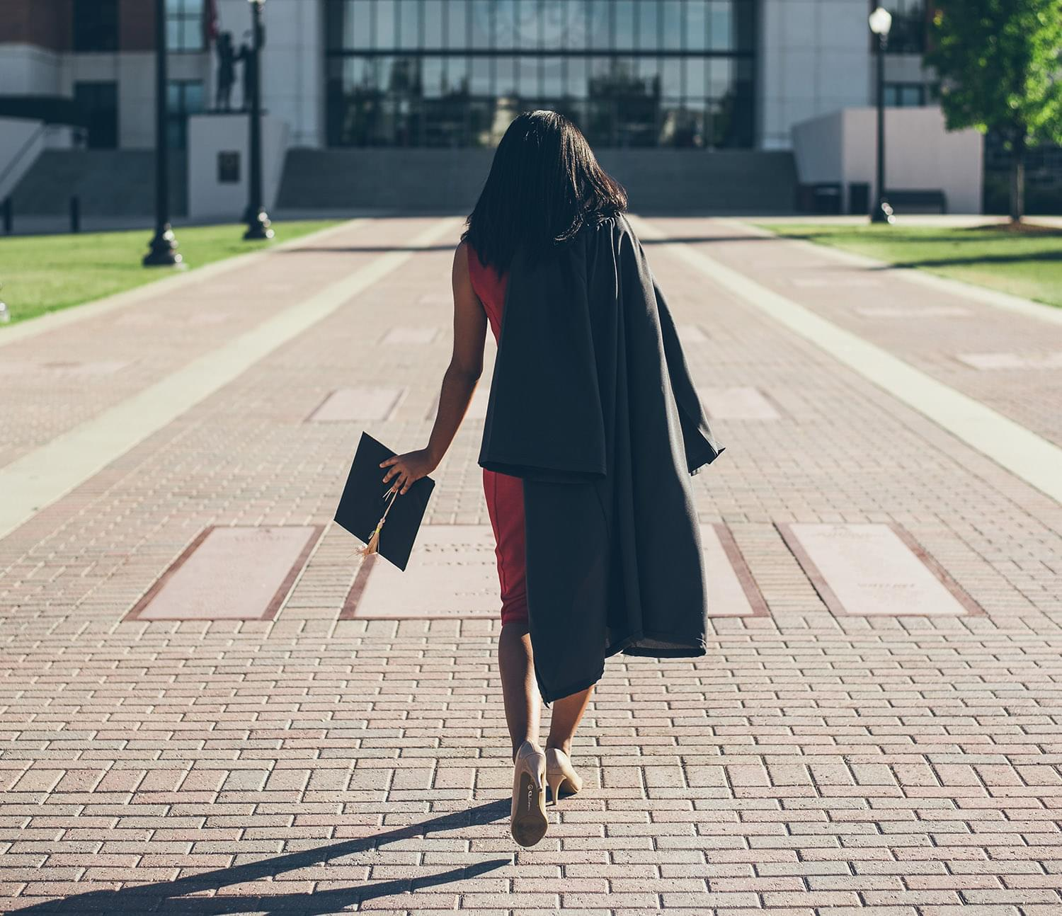 Recent graduate walking on campus with graduation cap and gown