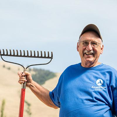 Man wearing an AmeriCorps T-shirt holding a rake