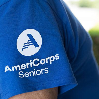 Close-up of the AmeriCorps Seniors logo on a blue T-shirt