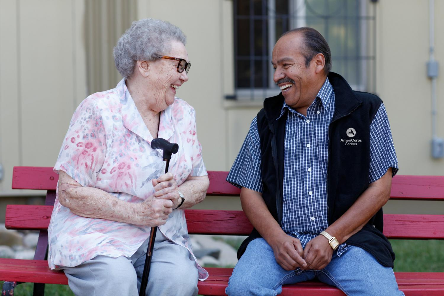 An AmeriCorps Seniors volunteer talks to a smiling woman