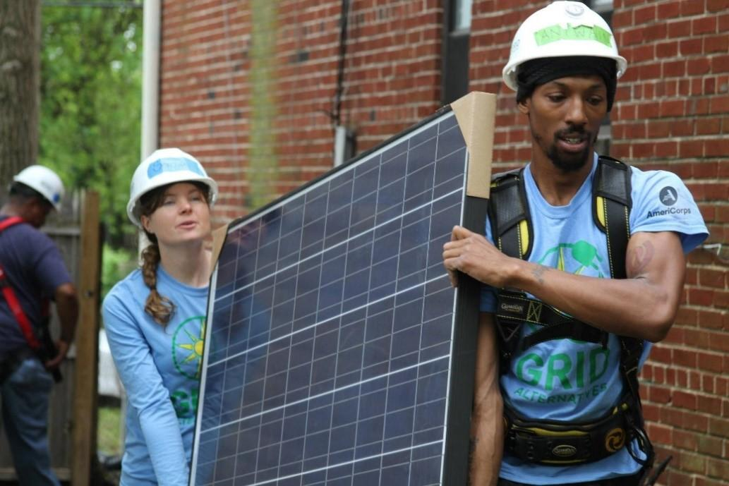 Two AmeriCorps members carry a solar panel