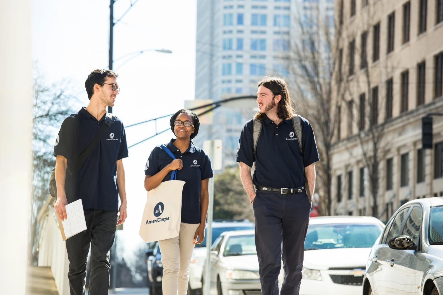 Three AmeriCorps members walking on sidewalk