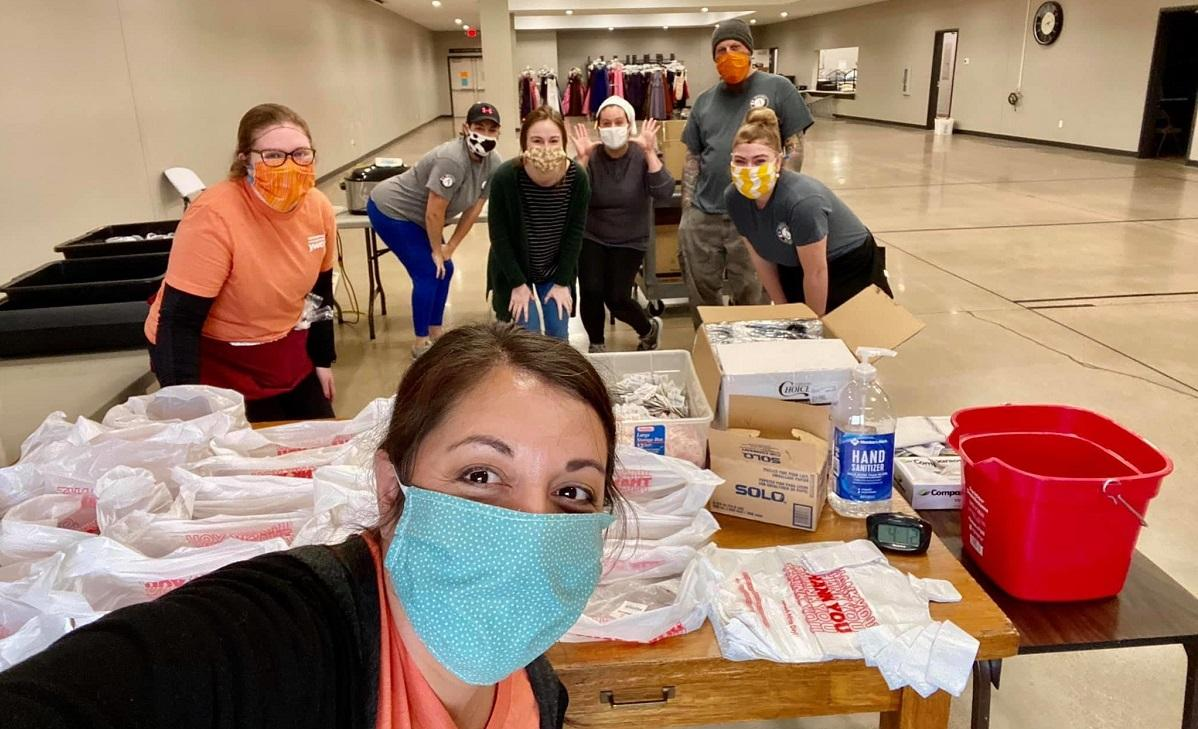 AmeriCorps members with safety masks stop to pose as they prepare care packages